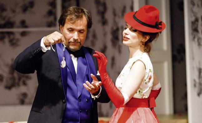 Eisenstein (Sebastian Reinthaller) demonstriert das Ührchen seiner schönen Dienstbotin Adele (Katharina Melnikova).